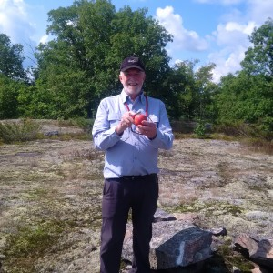 Picture of President David Mason on a rock base, cutting an apple.
